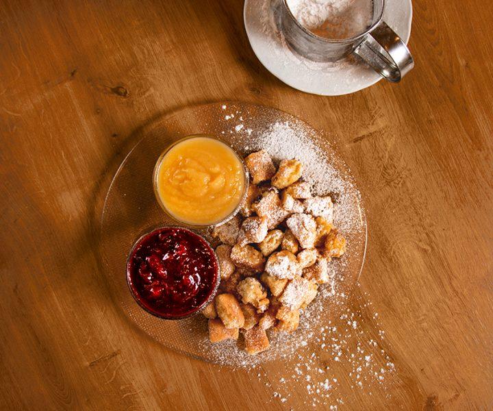 Teller Kaiserschmarren mit Extra-Staubzucker auf einem Tisch