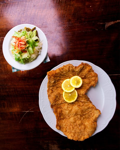 Plate of schnitzel and side salad on a table