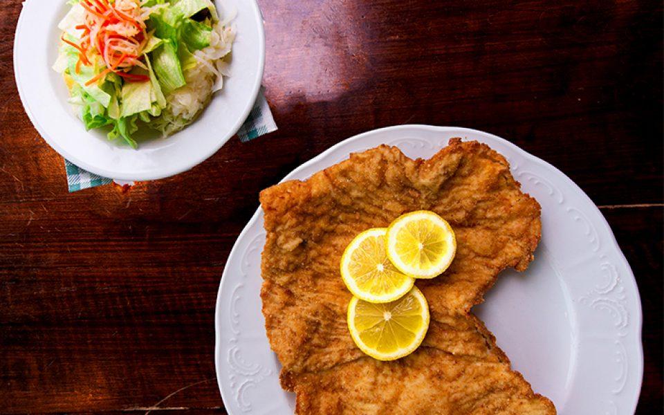 Schnitzelteller und Beilagensalat auf einem Tisch