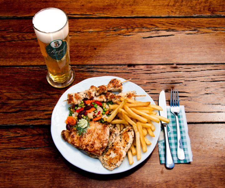 Teller mit Gegrilltem und Pommes sowie Bier und Besteck auf einem Tisch