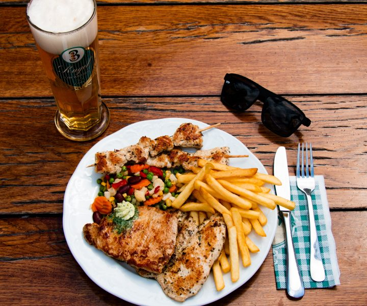Grilled meat plate with fries, vegetables, beer and sunglasses on a table